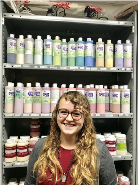 Ms. Reid cheerfully smiles while surrounded by art supplies in her classroom.