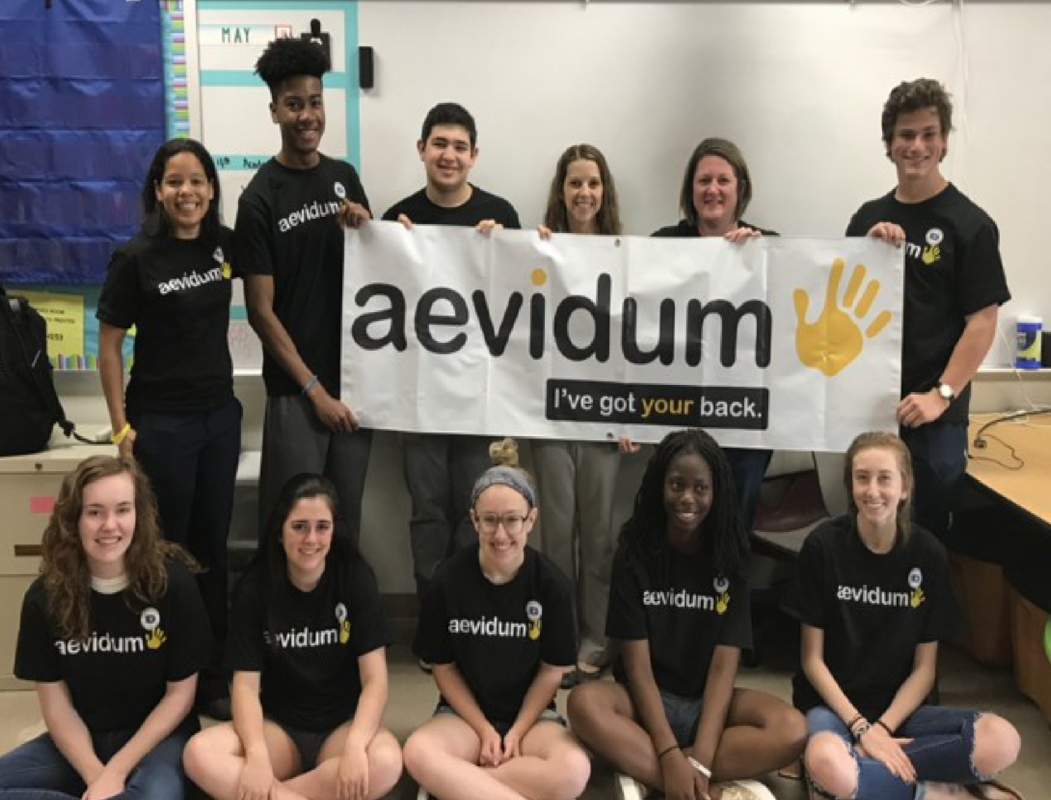 They've got our backs!  Aevidum students and advisers proudly display the club's logo and slogan at a May 2018 meeting.