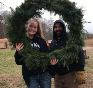 Showing off their artwork, seasonal employees Mackenzie and Greg share a laugh while presenting one big wreath!