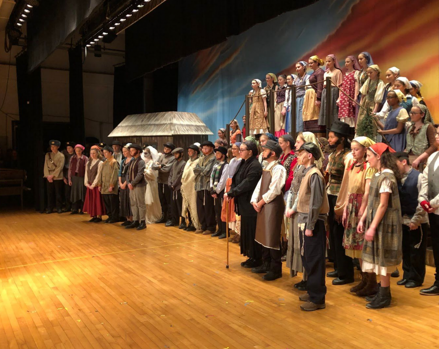 Lining the stage proudly, the cast and crew of DMS' production of Fiddler on the Roof take to the stage.
